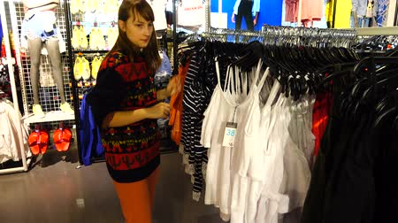 advertizing : Shopping in outlets Europe. The girl chooses clothes. Sale and discounts.