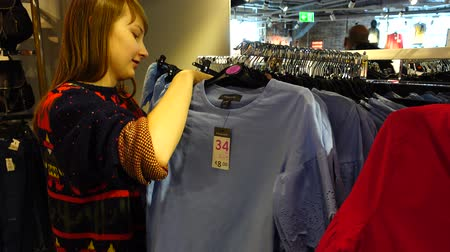 undershirt : Shopping in outlets Europe. The girl chooses clothes. Sale and discounts.