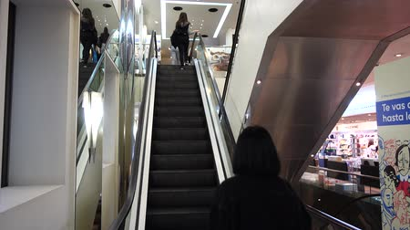 corte : MADRID, SPAIN - MARCH 27, 2018: Unknown people on the escalator in the shopping center El Corte Ingl?s.