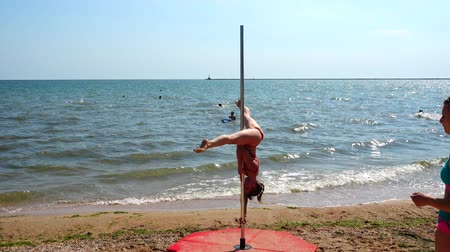 duygusallık : BERDYANSK, UKRAINE - JUNE 10, 2018: Participants of the All-Ukrainian Championship on the Pole Dance PD SUMMER at a public photo session on a public beach. Stok Video