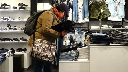 társult : Woman chooses clothes in shop. Shopping in shop.