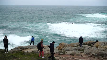 burza : LA CORUNA, SPAIN - APRIL 1, 2018: Unknown people look from the rocks at the ocean. La Coruna the largest city in the northwest of Spain, the resort and the port. Slow motion.