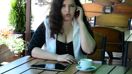 diner : The young and beautiful girl at a table in cafe and with phone Stock Footage