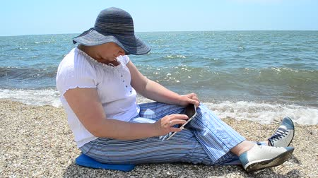 headwear : The girl with the tablet on the seashore