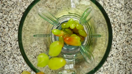 harmanlanmış : Grapes fall in a blender bowl. Slow motion. Shooting in kitchen. Top view. Stok Video