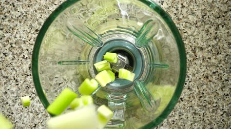 mashing : Stalk of an apium in a blender bowl. Slow motion. Shooting in kitchen. Top view.