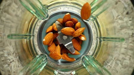 harmanlanmış : Falling of almonds in a blender bowl. Slow motion. Top view.