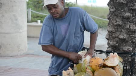 ivászat : MIAMI, USA - MARCH 26, 2014: The man cleans a coco publicly.