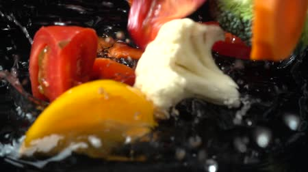 clear liquid : Vegetable mix from tomato, cauliflower, broccoli, pepper and carrots. Slow motion. Stock Footage