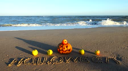 pigwa : Spooky halloween pumpkin. Inscription Halloween on the beach. Sea and waves. Shooting in October.
