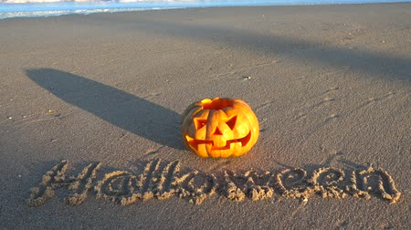 jack olantern : Spooky halloween pumpkin. Inscription Halloween on the beach. Sea and waves. Shooting in October.