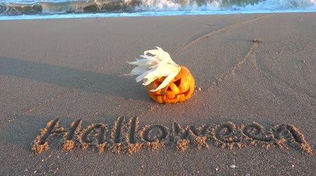 outubro : Spooky halloween pumpkin. Inscription Halloween on the beach. Sea and waves. Shooting in October.