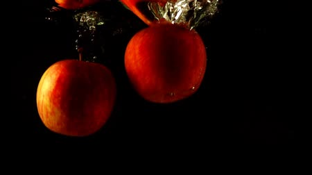 black and red : Falling of apples in water. Slow motion.