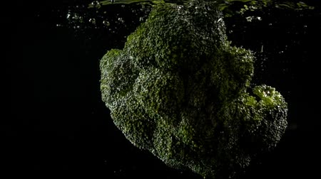 brocoli : Het vallen van kool van broccoli in water. Slow motion.
