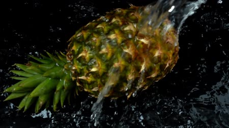 siyah üzerine izole : Water flow on pineapple. Slow motion.