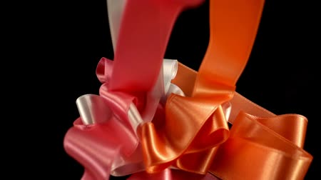 serpentine : Satin ribbon on a black background. Slow motion.