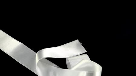 yılantaşı : Satin ribbon on a black background. Slow motion.