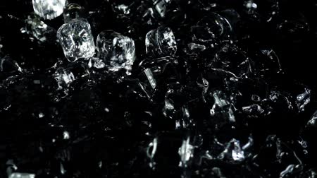 リフレッシュ : Falling cubes of ice on a black background. Slow motion.