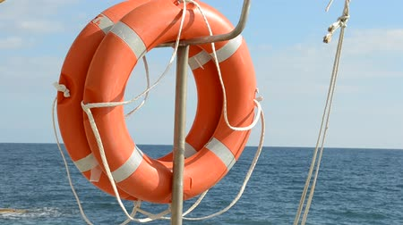 lifebuoy : Life ring floating on top of sunny blue water Stock Footage