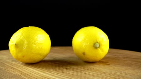 cítrico : Lemons on a black background. Cutting board in the movement.