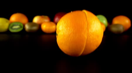 kivi : Falling of oranges against the background of fruit. Slow motion. Stok Video