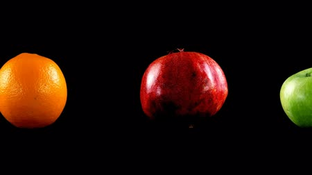 melograno : Pomegranate, apple and orange on a black background. Filmati Stock