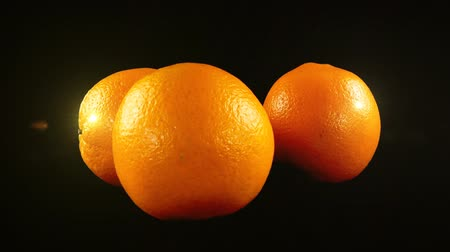 abundância : Oranges on a black background.