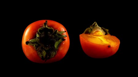 persimmons : Persimmon on a black background.