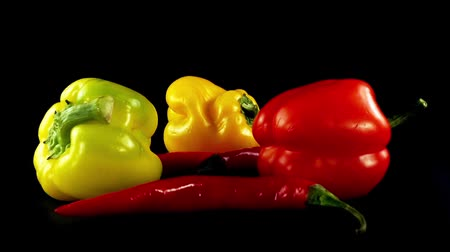 chili : Sweet pepper and chili pepper on a black background. Shooting in the movement. Stock mozgókép