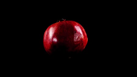 гранат : Pomegranate on a black background. Shooting in the movement.