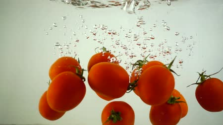 frescura : Cherry tomatoes fall in water. Slow motion. Vídeos