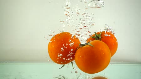 frescura : Tomatoes fall in water. Slow motion. Vídeos
