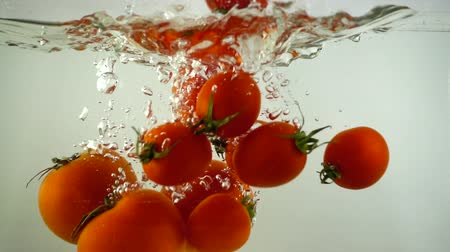 frescura : Tomatoes and cherry tomatoes fall in water. Slow motion.
