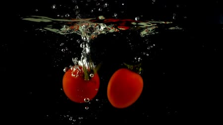 tomates cereja : Cherry tomatoes fall in water. Slow motion. Vídeos