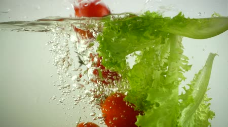 marul : Lettuce leaves and cherry tomatoes fall in water. Slow motion.