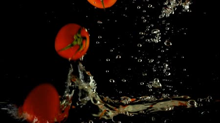 fejest ugrik : Cherry tomatoes in water. Slow motion.