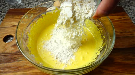legyintés : Addition of icing sugar in yolks. Preparation of custard. Slow motion. Stock mozgókép
