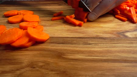 picada : Cook cuts carrots on a cutting board.