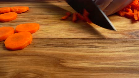 placa de corte : Cook cuts carrots on a cutting board.