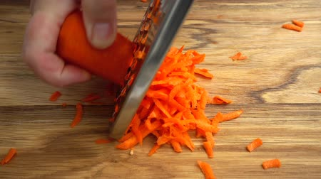 shred : The cook rubs carrots on a grater. Slow motion. Stock Footage