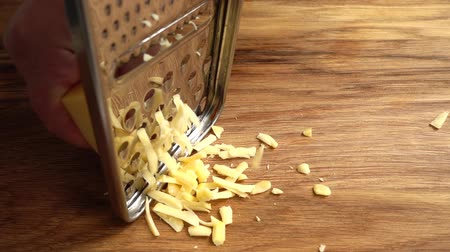 grated : The cook rubs cheese on a grater. Slow motion. Stock Footage