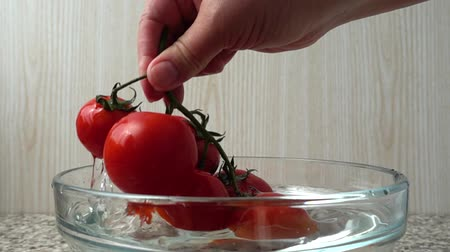 kap : The cook gets tomatoes from a bowl with water. Slow motion.