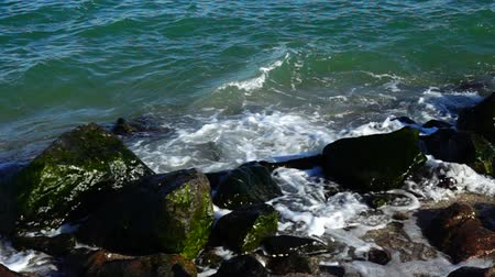 serenidade : Sea waves break against stones. Shooting on the seashore. Slow motion.