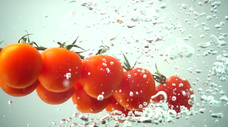 fejest ugrik : The falling cherry tomatoes in water. Slow motion.