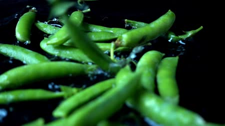 pea pods : Falling of water on a black background. Slow motion.