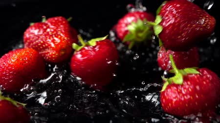 sabor : The falling strawberry in water on a black background. Slow motion.