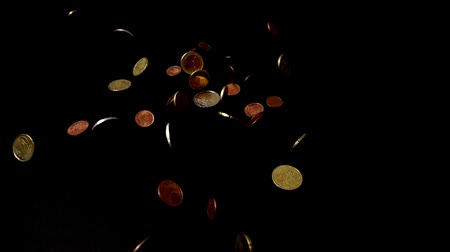 cent : Coins fall on a black background. Slow motion.