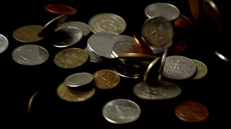 penny : Coins fall on a black background. Slow motion.