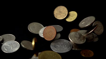 centavo : Coins fall on a black background. Slow motion.