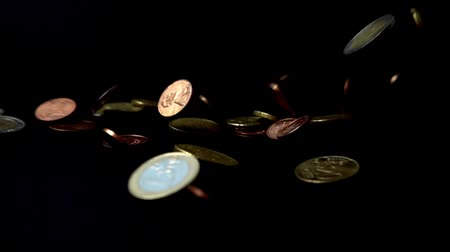пожертвование : Coins fall on a black background. Slow motion.